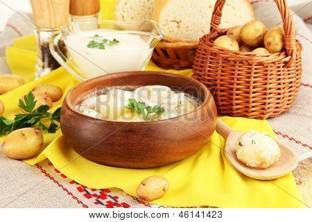 Concursos jovens batatas com creme de leite e ervas em uma tigela de madeira em close-up de toalha de mesa