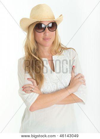 Hermosa joven con gafas de sol, sombrero de paja y kaftan blanco