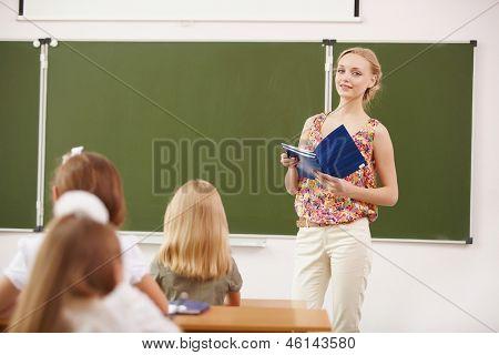 Young female teacher standing near blackboard at school