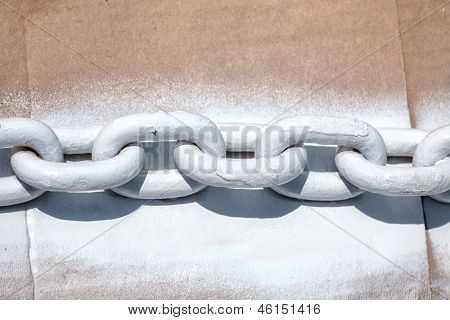Links of heavy duty ship chain laying on cardboard and spray painted.