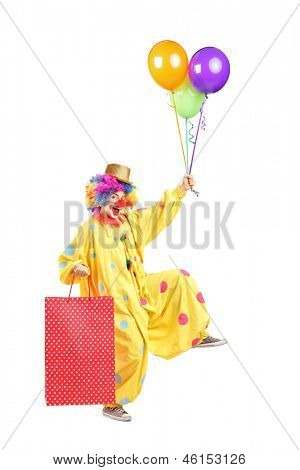 Full length portrait of a cheerfull clown with balloons and paper bag, isolated on white background