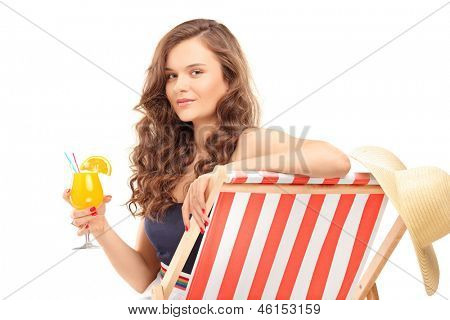 Young female sitting on a sun lounger and drinking a cocktail, isolated on white background