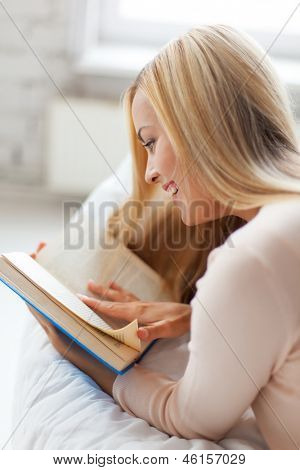 smiling woman lying on the sofa and reading book