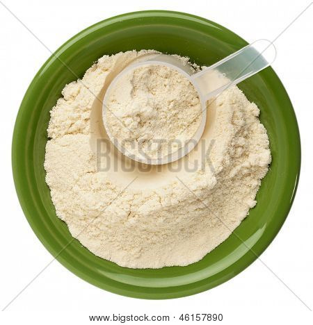 whey protein powder in a small ceramic bowl with a plastic scoop