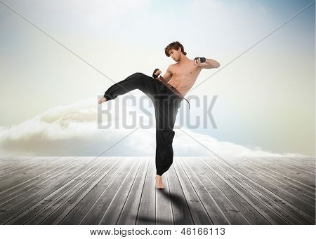 Martial arts fighter over wooden boards leading out to the horizon