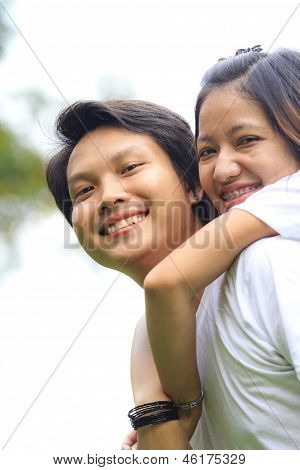 Young Woman Embracing Man From Behind In Park