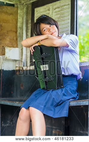 Cute Thai Shoolgirl Is Daydreaming In An Old Bus Stop
