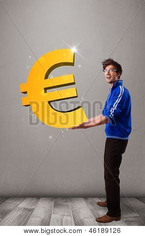 Good-looking young boy holding a big 3d gold euro sign
