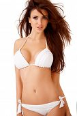 Sexy curvy young brunette woman with large breasts posing in a white bikini  three quarter isolated