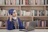 stock photo of muslimah  - Asian female muslim thinking at library in blue dress - JPG