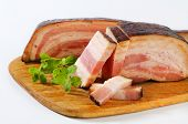 portioned smoked block of bacon on a wooden cutting board