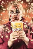 stock photo of gruesome  - Frightened female ghoul splashing popcorn everywhere at a fright night slasher flick - JPG