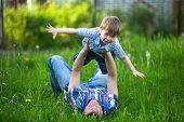 stock photo of father child  - Father and son playing lying on the grass in the park - JPG