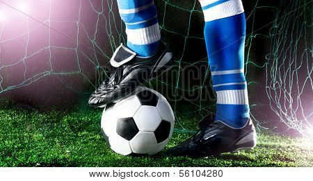 Soccer player's feet in casual pose on playing field with dark background