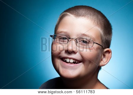 A portrait of a young boy with glasses smiling