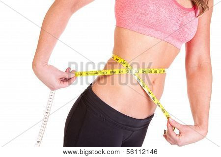 A beautiful young woman using a tape measure to measure her slim waist size on a weight management p