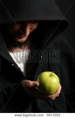Portrait of young man holding shiny fresh green apple
