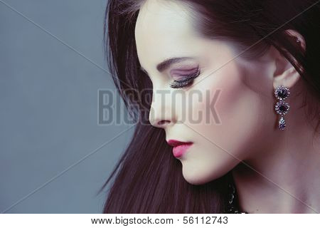 Dramatic portrait of beautiful woman with long dark hair and artistic makeup on studio background