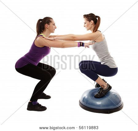 Woman Doing Squats On A Bosu Ball, Helped By The Peronal Trainer