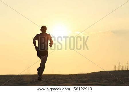 Backlight Of A Jogger Running On The Beach