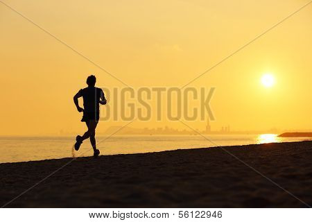 Jogger Silhouette Running On The Beach At Sunset