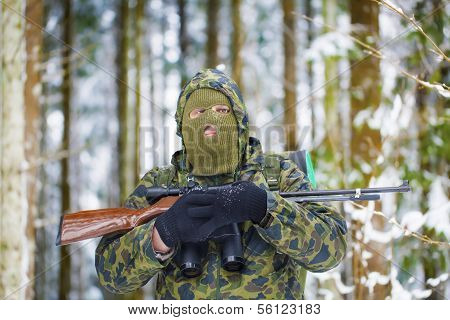 Hunter with optical rifle and binoculars forest in the winter