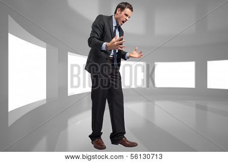 Stressed businessman gesturing against bright room with windows