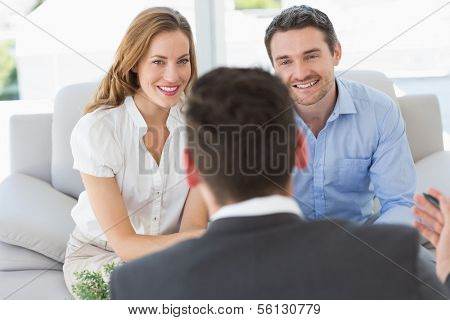 Smiling young couple in meeting with a financial adviser at home
