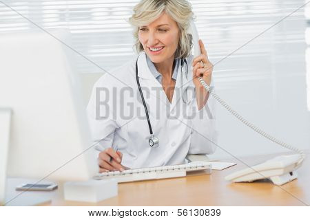 Smiling female doctor with computer using phone at medical office