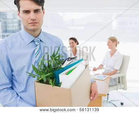 Portrait of a young businessman leaving office with his belongings and colleagues in background