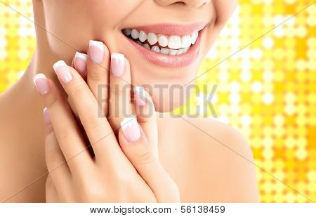 face, hands and healthy white teeth of a woman, bright gold background
