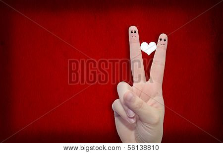 Two hands with fingers and a heart painted over a red paper vintage and grungy background
