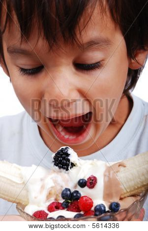 Very cute kid about to eat colorful cake isolated