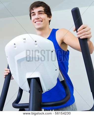 Happy Young Man With Elliptic Machine In The Gym