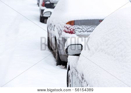 Snow covered cars in city