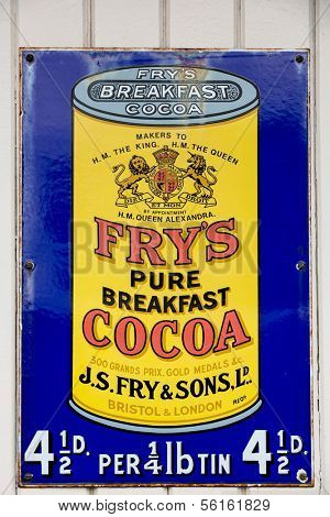 NR SOUTHAMPTON,UK - 25 June 2013: Old style tin advertising board for Fry's Cocoa displayed on painted wood background. On 25 June 2013 Near Southampton UK