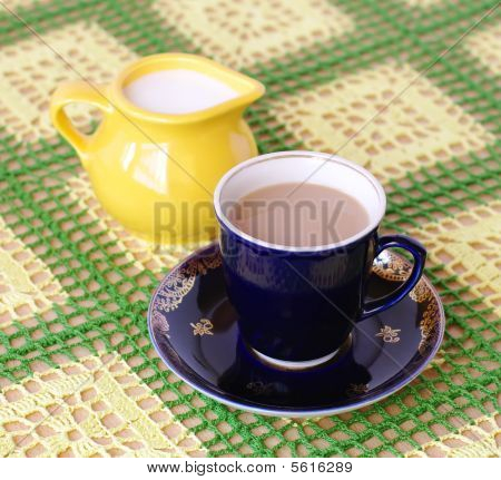 Cup Of Beverage Jug With Milk And Teapot On Backplane
