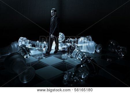 Businessman on a chessboard walk from the capsized dummies