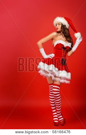 Full length portrait of an attractive young woman in Santa Claus costume over red background. Christmas.