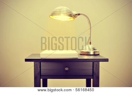 picture of an old gooseneck lamp and a stack of blank paper sheets on a bureau, with a retro effect