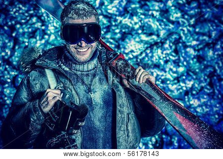 Smiling handsome man dressed in winter clothes, holding skiing, covered with frost.