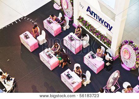 Hostessen von Amway beraten die Kunden ihre Produkte veranschaulicht