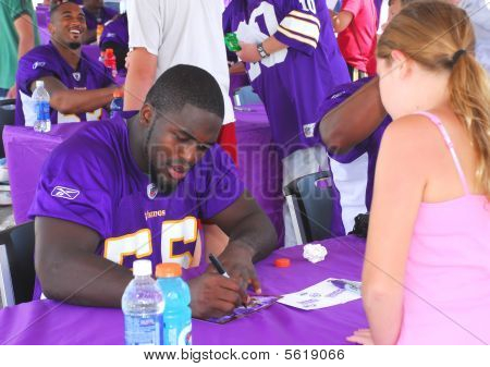 Minnesota Vikings Linebacker Kenny Onatolu assina autógrafos.