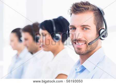 Side view of a group of business colleagues with headsets in a row at office