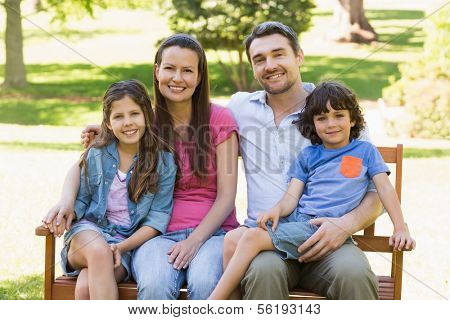 Portrait of a smiling couple with young kids sitting on park bench