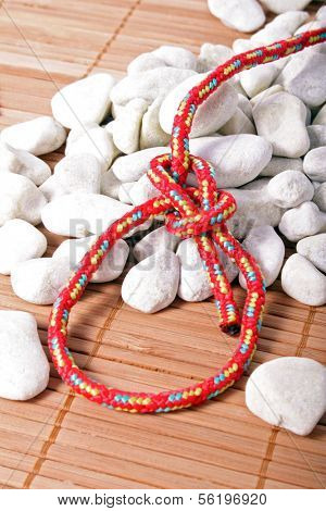 A fine knotted bowline next to a pile of stones