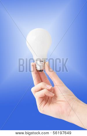 A human hand holding a bulb in front of a white to blue gradient