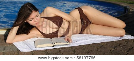 An attractive young woman wearing a bikini and reading a book next to the swimming pool