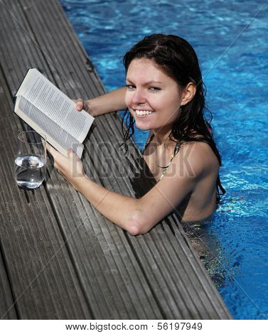 An attractive young woman wearing a bikini and reading a book in the swimming pool