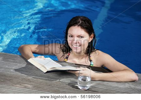 An attractive young woman wearing a bikini and reading a book in the swimming pool.